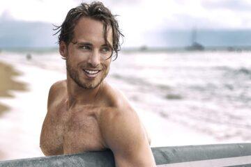 surfista-con-la-tabla-en-la-mano-sonriendo-blanqueamiento-dental